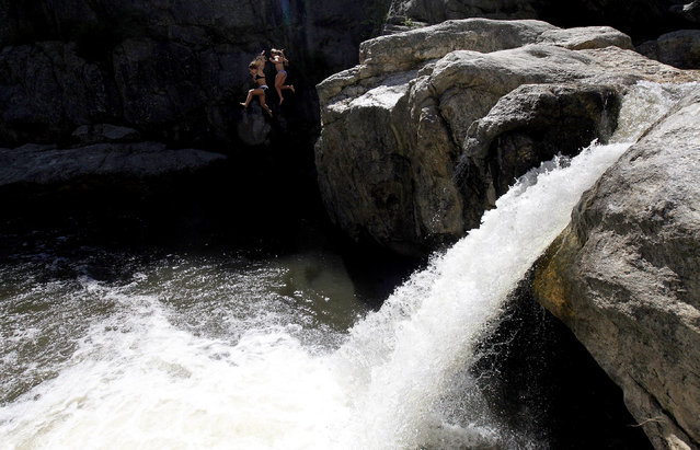 Sarah Houghland, 15, and Hannah Wang, 16, jump off the rocks at a popular swimming spot on Battle Creek locally known as Hippie Hole, Tuesday afternoon, June 10, 2014. The cool creek waters provided some reprieve from a high temperature of nearly 80 degrees. (Photo by Chris Huber/AP Photo/Rapid City Journal)