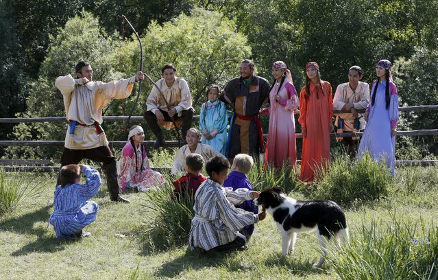 Members of national folklore and ethnographic groups and employees of a museum-preserve participate in the reconstruction of daily life and traditional holidays celebrated by indigenous population of the Republic of Khakassia during a demonstration for visitors outside Kazanovka village, southwest of the city of Abakan, Russia, July 24, 2015. (Photo by Ilya Naymushin/Reuters)