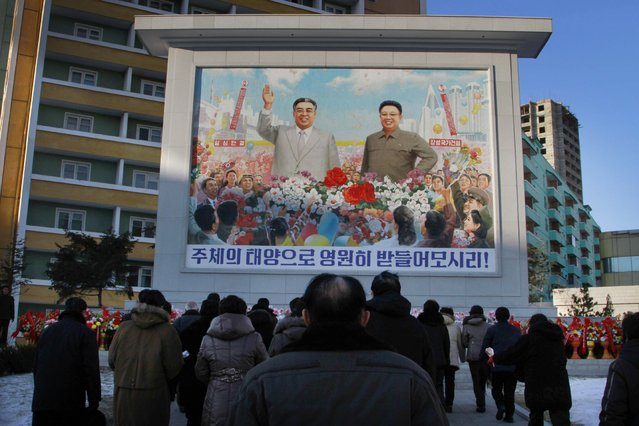 North Koreans gather in front of a portrait of their late leader Kim Il Sung, left,  and Kim Jong Il, right, paying respects to their late leader Kim Jong Il, to mark the third anniversary of his death, Wednesday December 17, 2014 at Pyong Chon District in Pyongyang, North Korea. North Korea marked the end of a three-year mourning period for the late leader Kim Jong Il on Wednesday, opening the way for his son, Kim Jong Un, to put a more personal stamp on the way the country is run. (Photo by Kim Kwang Hyon/AP Photo)