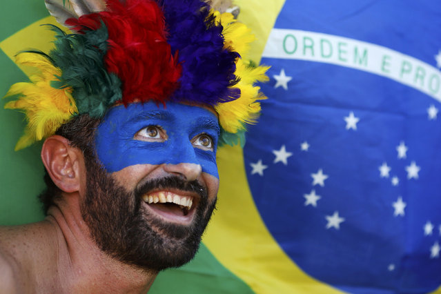 A soccer fan poses in front of a Brazilian flag ahead of their group D 2014 World Cup match against England at the Arena da Amazonia stadium in Manaus, June 14, 2014. (Photo by Siphiwe Sibeko/Reuters)