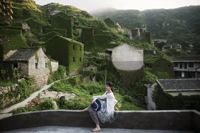 A tourist poses for photos in the abandoned fishing village of Houtouwan on the island of Shengshan July 25, 2015. (Photo by Damir Sagolj/Reuters)