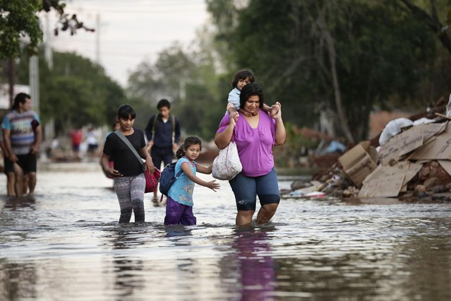 Victoria Barreto and her children wade through a flooded street to get to their school, in the Banado Norte neighborhood, in Asuncion, Paraguay, Thursday, July 30, 2015. Authorities reported that among the marshes north and south of Asuncion, 37,000 people have been displaced due to cyclical flooding of the Paraguay River. (Photo by Jorge Saenz/AP Photo)