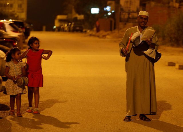Girls look on and listen to their names as El Mesaharty, Hussien, 40, wakes up residents for their pre-dawn meals during the first day of Ramadan in Cairo, Egypt June 6, 2016. (Photo by Amr Abdallah Dalsh/Reuters)