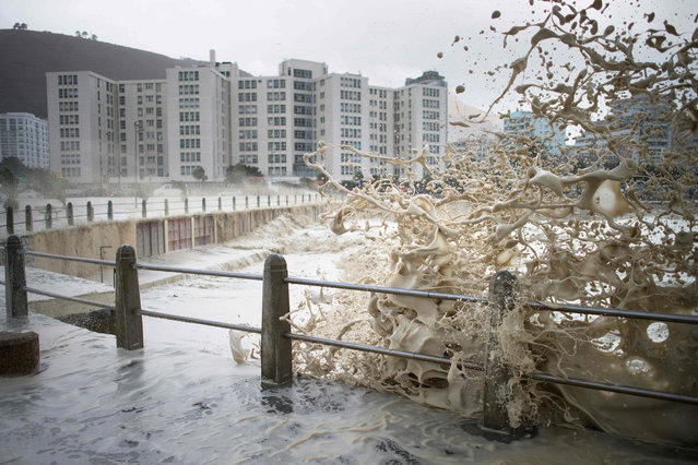 Waves of foam and seawater crash into Three Anchor Bay in Cape Town on June 7, 2017, as an intense storm hits South Africa' s west coast. The ferocious storm killed eight people as it pummelled South Africa' s west coast on Wednesday, forcing the closure of Cape Town harbour, triggering flash floods and causing extensive damage, authorities said. The weather system which struck on June 6 has damaged buildings, felled trees, left 46,000 homes without electricity and caused travel chaos as flights and rail services were hit by gale- force winds and flooding. (Photo by Rodger Bosch/AFP Photo)