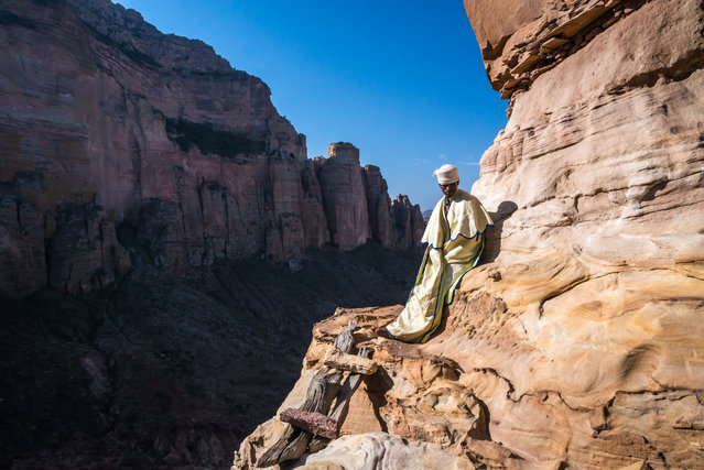 """""""Priest, Gheralta"""". The church of Abuna Yemata is hidden in a cave atop a 200m vertical cliff. Such are the churches of Gheralta, Ethiopia, carved out of the sides of mountain tops where the priests can reside closer to the heavens and away from the worries of the lands below. With my camera bag on my back I sweated my way up the cliff to find the priest proud in his Sunday best, standing on a ledge only 2 meters wide. Photo location: Ethiopia. (Photo and caption by Chris Roche/National Geographic Photo Contest)"""