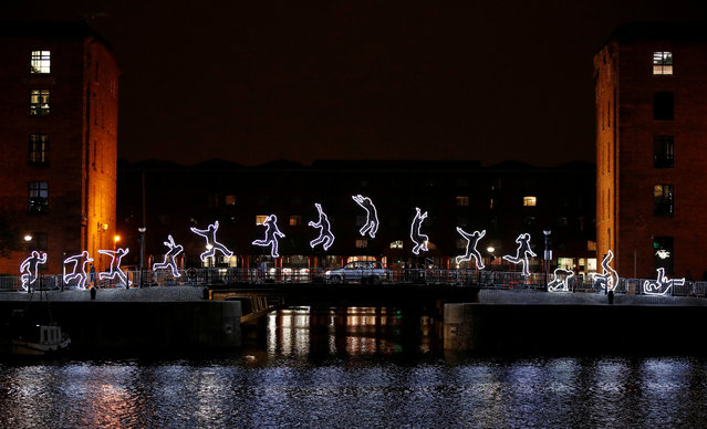 """An car drives past an installation called """"Run Beyond"""" which forms part of the River of Light festival in Liverpool, Britain, October 31, 2019. (Photo by Phil Noble/Reuters)"""