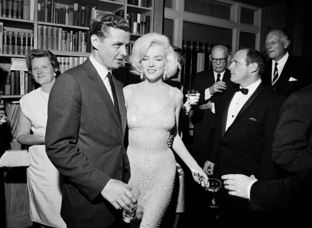 """In this May 19, 1962 photo provided by the John F. Kennedy Presidential Library and Museum, actress Marilyn Monroe wears the iconic gown that she wore while singing """"Happy Birthday"""" to President John F. Kennedy at Madison Square Garden, during a reception in New York City. Standing next to Monroe is Steve Smith, President Kennedy's brother-in-law. Julien's Auctions will offer Monroe's gown at auction in Los Angeles on Nov. 17, 2016. (Photo by Cecil Stoughton/White House Photographs, John F. Kennedy Presidential Library and Museum via AP Photo)"""