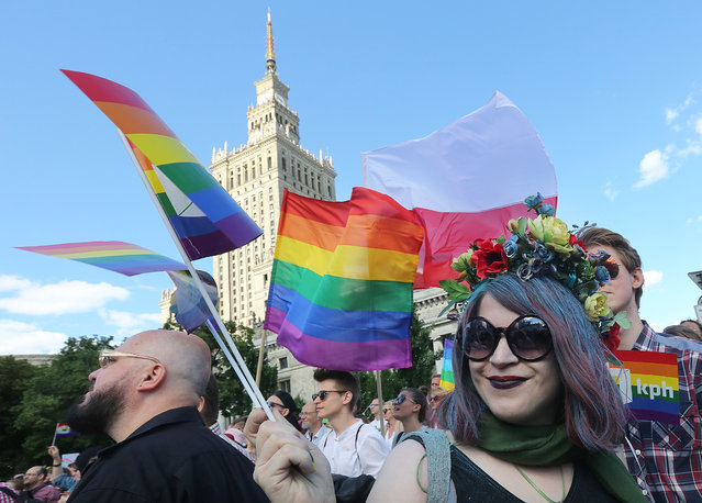 Thousands of Warsaw residents with rainbow flags walk in a colorful annual Equality Parade to show their support for sexual minority groups  in Warsaw, Poland, Saturday, June 11, 2016. The 16th parade Saturday is held at a time when views concerning minorities are getting radicalized under a right-wing government that took office in November. A visible police presence accompanied the march. (Photo by Czarek Sokolowski/AP Photo)