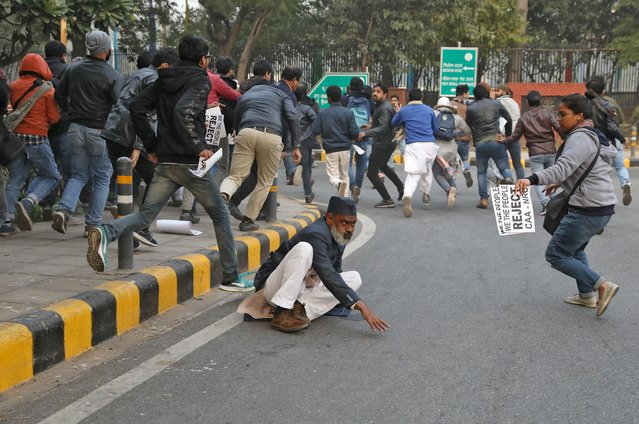 A man falls as demonstrators are chased by police (unseen) during a protest against a new citizenship law, in New Delhi, India, December 27, 2019. (Photo by Anushree Fadnavis/Reuters)