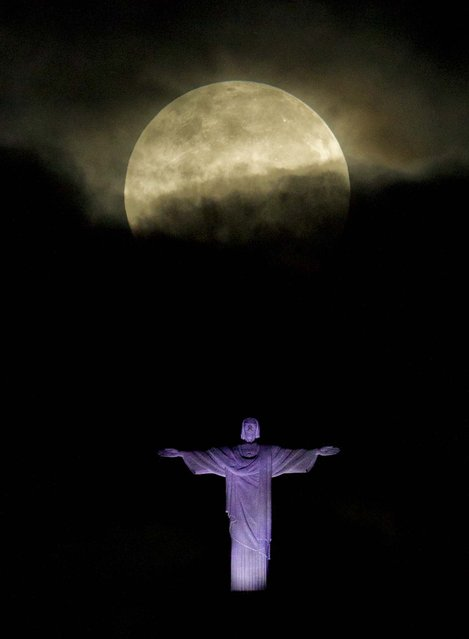 The Supermoon – the moon made its closest approach of the year to Earth – appears above the Christ the Redeemer statue in Rio de Janeiro on May 6, 2012