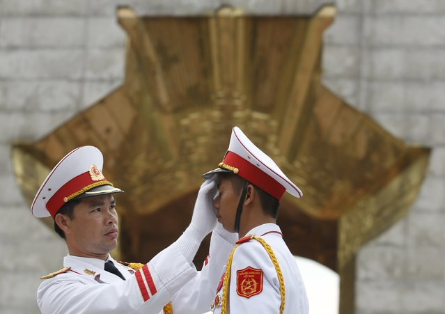 A Vietnamese military officer (L) adjusts the hat of a honour guard member before a wreath-laying ceremony attended by Bangladesh's President Abdul Hamid (not pictured) at the Monument to War Heroes and Martyrs in Hanoi, Vietnam August 9, 2015. (Photo by Reuters/Kham)