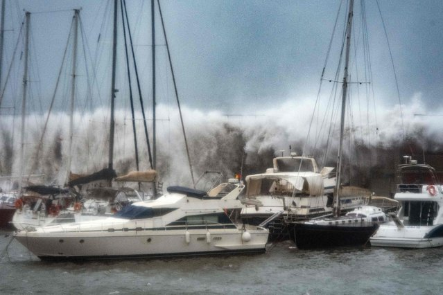 Big waves overpass a breakwater at the Port Olympic marina in Barcelona as storm Gloria batters Spanish eastern coast on January 21, 2020. Freezing winds, heavy snow and rain lashed parts of Spain yesterday, killing three people, forcing the closure of schools that cancelled classes for nearly 200,000 students and disrupting travel, officials said. (Photo by Josep Lago/AFP Photo)