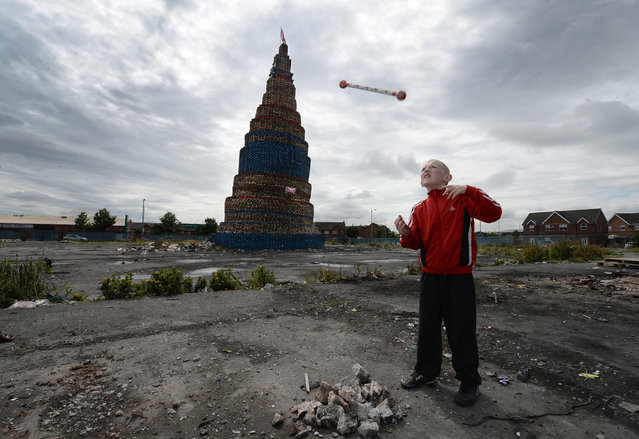 Curtis Walker throws his protestant band baton beside a Loyalist pyre on Lanark Way as final preparations are made for the 11th night bonfire, on July 11, 2014 in Belfast, Northern Ireland. The bonfire at Lanark Way, the tallest in Northern Ireland, stands at over 200ft high and is made of pallets gathered by Loyalists to mark the beginning of the annual 12th of July Orange parade. (Photo by Charles McQuillan/Getty Images)