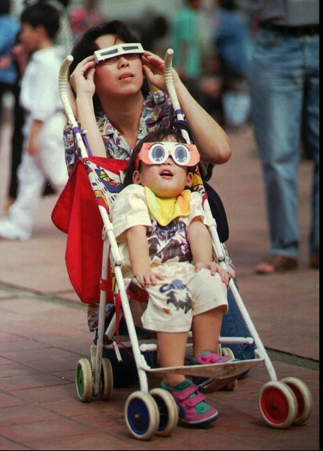 A child and mother don special protective glasses to view a partial solar eclipse in the Thai capital of Bangkok Tuesday, October 24, 1995. Tens of thousands of Thais surged to upcountry areas where the rare eclipse – seen along a band across the southern Asia landmass – was total. Doctors recommend viewers to wear special glasses to prevent eye damage. (Photo by Sakchai Lalit/AP Photo)