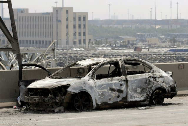 A damaged car is seen near the site of the explosions at the Binhai new district, Tianjin, August 13, 2015. (Photo by Jason Lee/Reuters)