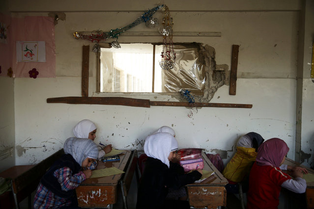 Girls attend a final exam inside a school in the town of Douma, eastern Ghouta in Damascus, Syria May 24, 2016. (Photo by Bassam Khabieh/Reuters)