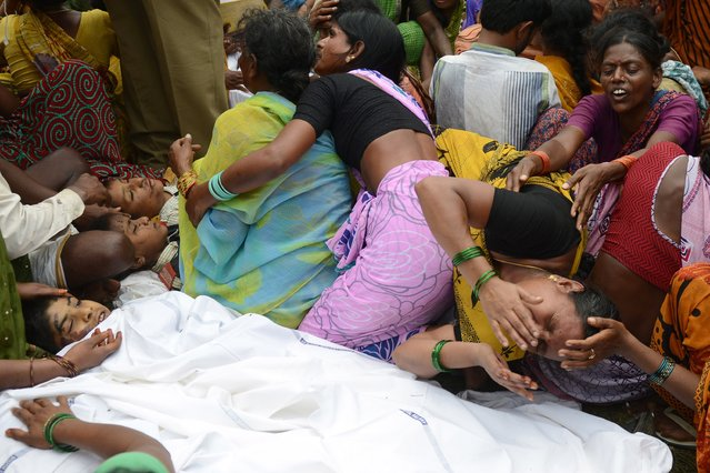 Indian families grieve over the bodies of their children at the site of the collision between a school bus and a train at Thoopran Mandal of Medak District, about 58 kilometers from Hyderabad, on July 24, 2014. A passenger train rammed into a school bus in southern India, killing at least 11 children, with fears the death toll could be as high as 25, officials said. (Photo by Noah Seelam/AFP Photo)