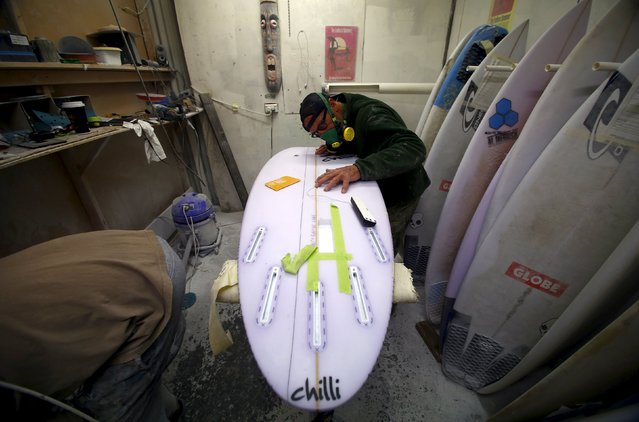 Surfboard repairman Will Burgess checks the alignment of a wire as he installs a shark repellent device in a board at his Sydney workshop in Australia, August 14, 2015. (Photo by David Gray/Reuters)