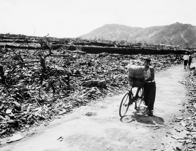A man pushes a loaded bicycle down a cleared path in a flattened area of Nagasaki, September 13, 1945, following the August 9 nuclear attack by an American B-29. (Photo by Stanley Troutman/AP Photo/ACME)