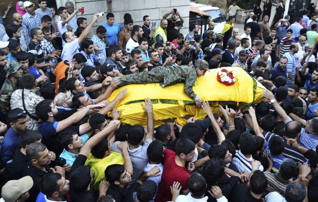 The son of Ibrahim al-Haj, a Hezbollah commander who died during a mission in Iraq, wears a military outfit as he lies on his father's coffin during his funeral in Mashghara village in the Bekaa Valley, July 30, 2014. (Photo by Shawky Haj/Reuters)