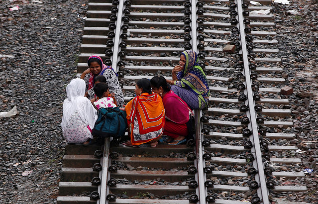 Women sit on railway tracks as they wait to board a passenger train to travel home to celebrate Eid al-Fitr festival, which marks the end of the Muslim holy fasting month of Ramadan, at a railway station in Dhaka, Bangladesh, July 5, 2016. (Photo by Adnan Abidi/Reuters)