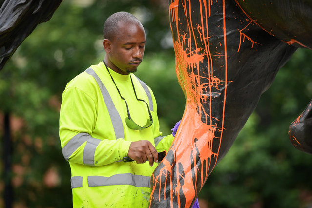A municipal worker attempts to remove paint from a monument dedicated to Confederate soldier John B. Castleman that was vandalized late Saturday night in Louisville, Kentucky, U.S., August 14, 2017. (Photo by Bryan Woolston/Reuters)