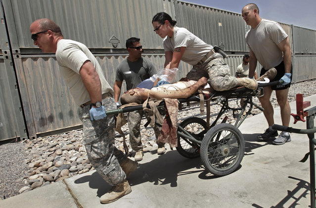 Hospital personnel attempt to revive a mortally wounded Marine after he was brought in by medevac helicopter at Camp Dwyer near the town of Marjah in Helmand Province, Afghanistan, August 22, 2010. (Photo by Bob Strong/Reuters)