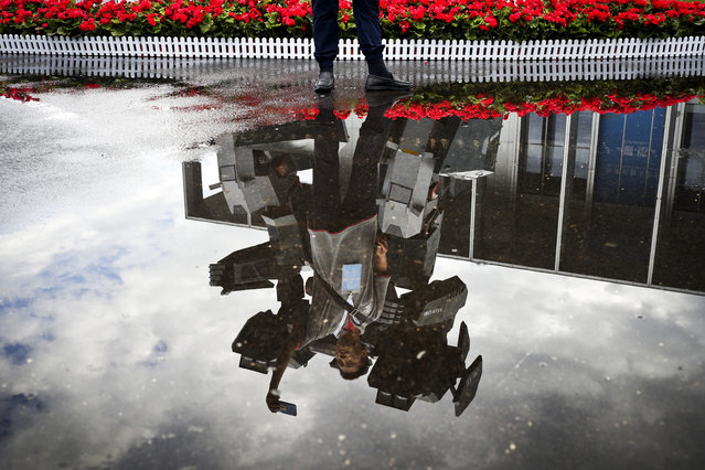 A man is reflected in a puddle of water with a robot on display at the Yichuang International Conference and Exhibition Centre during the World Robot Conference held in Beijing, Wednesday, August 23, 2017. (Photo by Andy Wong/AP Photo)
