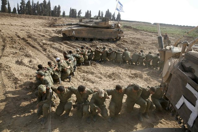 Israeli soldiers from the armoured corps kneel together next to tanks after returning to Israel from Gaza August 5, 2014. Israel pulled its ground forces out of the Gaza Strip on Tuesday and started a 72-hour ceasefire with Hamas mediated by Egypt as a first step towards negotiations on a more enduring end to the month-old war. (Photo by Baz Ratner/Reuters)
