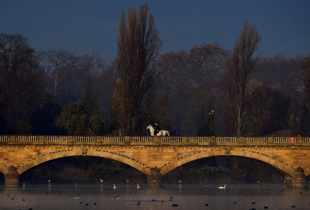 Horse riders cross a bridge over the Serpentine lake in Hyde Park, London, Britain, November 19, 2019. (Photo by Toby Melville/Reuters)