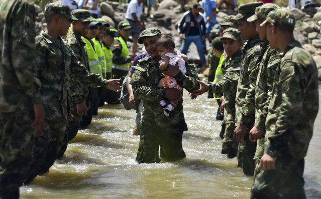A baby is carried across the bordering Tachira River by a soldier as hundreds of Colombians leave Venezuela with their belongings, arriving in Cucuta, Colombia, on August 27, 2015. Hundreds of Colombians are fleeing Venezuela, opting to leave the country with their belongings rather than be deported empty-handed like more than 1,000 people sent home in an escalating border crisis. (Photo by Luis Acosta/AFP Photo)