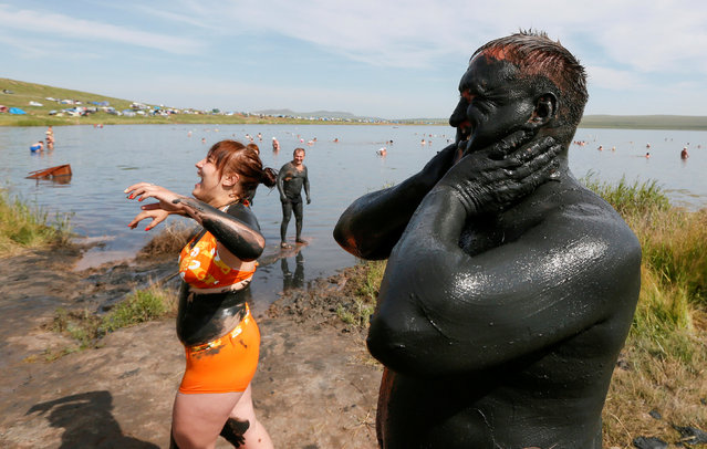 Tourists rest as they cover themselves with mineral-rich mud on a bank of lake Tus in Khakassia region, southwest of the Siberian city of Krasnoyarsk, Russia, July 16, 2016. (Photo by Ilya Naymushin/Reuters)