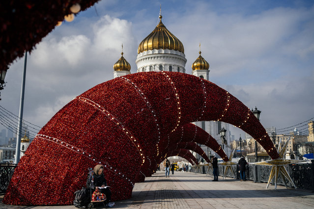 An elderly woman reads while selling traditional Russian wooden nesting dolls, called Matryoshka dolls, on a bridge over the Moskva river in front of the Cathedral of Christ the Saviour in downtown Moscow on March 4, 2020. (Photo by Dimitar Dilkoff/AFP Photo)