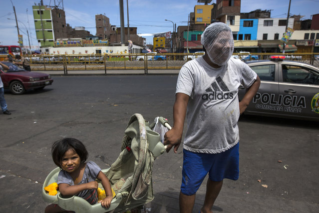 In this March 19, 2020 photo, Luis Mendoza jokingly dons a hair net over his face given to him by a group handing out protective gear outside a popular market where he has come to beg for food with his 2-year-old daughter Alejandra, in Lima, Peru. The global COVID-19 pandemic has spotlighted the wide gap between the rich and poor in Latin America and economists say a looming economic recession worse than any since World War II could push the continent's long-suffering poor into even more dire circumstances.(Photo by Rodrigo Abd/AP Photo)