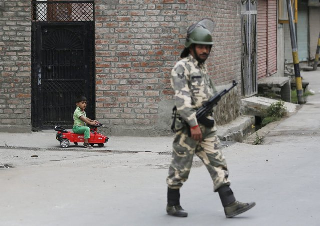 A Kashmiri child rides a toy vehicle as an Indian paramilitary soldier stand guard during a curfew in Srinagar, the summer capital of Indian Kashmir, 22 July 2016. The authorities imposed strict curfew and severe restrictions in most parts of Kashmir valley for the 14th consecutive day to contain protests following the killing of Hizb-ul-Mujahideen commander Burhan Muzaffar Wani. Photo by Farooq Khan/EPA)