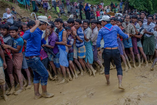 Bangladeshi men try to control Rohingya Muslims, who crossed over from Myanmar into Bangladesh, during the distribution of food aid near Kutupalong refugee camp, Bangladesh, Tuesday, September 19, 2017. With a mass exodus of Rohingya Muslims sparking accusations of ethnic cleansing from the United Nations and others, Myanmar leader Aung San Suu Kyi on Tuesday said her country does not fear international scrutiny and invited diplomats to see some areas for themselves. (Photo by Dar Yasin/AP Photo)