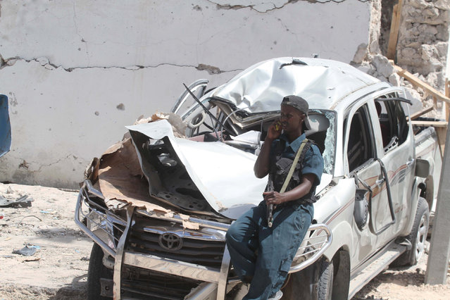 A policeman talks on his cellphone as he rests on the wreckage of a car destroyed during a suicide bombing near the African Union's main peacekeeping base in Mogadishu, Somalia, July 26, 2016. (Photo by Ismail Taxta/Reuters)