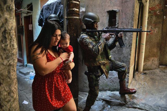A woman walks with her baby past a PM militarized police soldier in position and aiming his rifle in Rocinha favela in Rio de Janeiro, Brazil on September 23, 2017. Although shooting was reported in the early hours of Saturday in Rocinha – for the seventh day running – officials said that Friday's deployment of 950 soldiers to reinforce police had brought the crisis under control. (Photo by Carl De Souza/AFP Photo)
