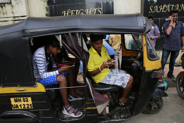 "In this Sunday, July 24, 2016 photo, Indians sit inside an autorickshaw and play ""Pokemon Go"" in Mumbai, India. ""Pokemon Go"", the highly addictive online game, has landed in India and thousands are out searching for pokemon characters as the mania spreads. Although it has not been launched officially in India, the augmented-reality-based game has caught on, with fans also using virtual private networks (VPNs) to change their locations and catch pokemons in New York and London while sitting in their Indian homes. (Photo by Rafiq Maqbool/AP Photo)"