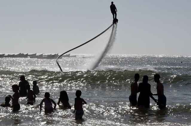 A man performs on a water-propelled flyboard on Sidi Bouzid Beach on August 16, 2014 in the Moroccan port city of El Jadida. (Photo by Fadel Senna/AFP Photo)