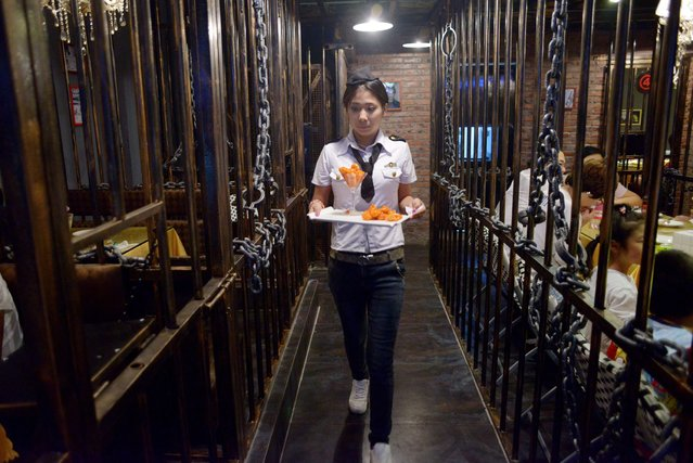 This picture taken on September 9, 2014 shows a waiter carrying food to customers at a prison themed restaurant in Tianjin. (Photo by Wang Zhao/AFP Photo)