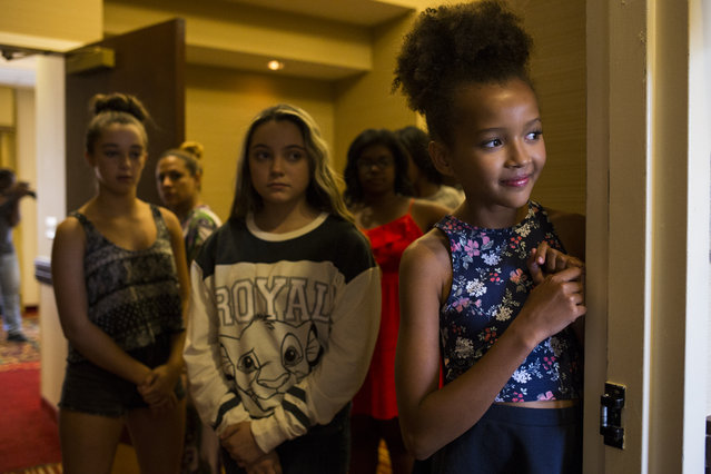 Aicha Bleers, 11, of Chevy Chase, Md., looks on as she and other camp attendees practice their runway walks at a modeling camp at the Courtyard Marriott Hotel in McLean, Va., on Tuesday, August 19th, 2015. (Photo by Brittany Greeson/The Washington Post)