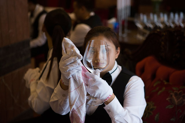 A butlery student polishes glassware in preparation for a formal dinner at The International Butler Academy China on September 16, 2014 in Chengdu, China. (Photo by Taylor Weidman/Getty Images)