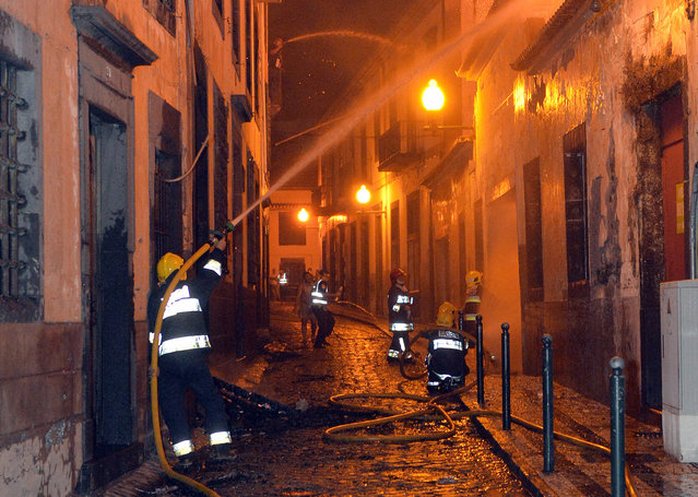 In this photo taken late Tuesday, August 9 2016, firefighters battle a fire that reached the old center of Funchal, the capital of Portugal's Madeira island. Forest fires in Madeira forced the evacuation of more than 1,000 residents and tourists. (Photo by Helder Santos/AP Photo)