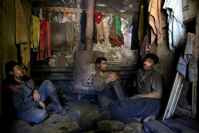 In this Tuesday, May 6, 2014 photo, Iranian coal miners rest during a break at a mine on a mountain in Mazandaran province, near the city of Zirab, 212 kilometers (132 miles) northeast of the capital Tehran, Iran. The miners put in long hours in often dangerous conditions and make just $300 a month, little more than minimum wage. (Photo by Ebrahim Noroozi/AP Photo)