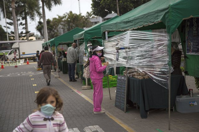 A woman talks to a vendor through a protective plastic due to COVID-19, in a street market in Barranco neighborhood, in Lima, Peru, Saturday, June 20, 2020. (Photo by Rodrigo Abd/AP Photo)