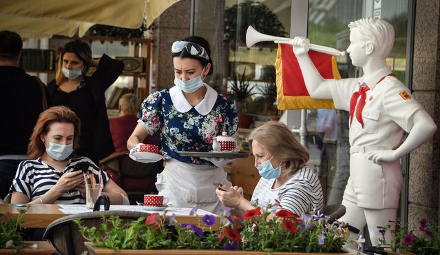 A waitress serves a meal in a Soviet style cafe in central Moscow on June 16, 2020, amid the outbreak of COVID-19, caused by the novel coronavirus. The city of Moscow allowed to start serving at the open terraces from June 16, 2020, easing the constraint regime. (Photo by Alexander Nemenov/AFP Photo)