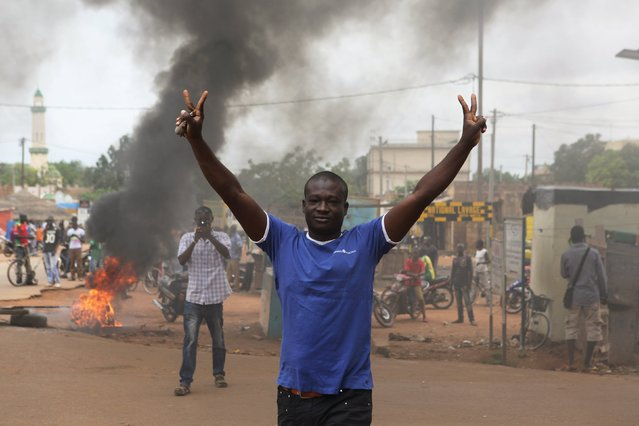 A protester gestures in front of a burning roadblock in Ouagadougou, Burkina Faso, September 18, 2015. Security forces in the capital of Burkina Faso fired in the air on Friday to disperse demonstrators who burned tyres and blocked neighborhood streets to protest at a military coup this week that derailed a democratic transition. (Photo by Joe Penney/Reuters)