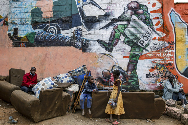 In this June 9, 2020, file photo, Kenyan children and men are photographed in the Kibera slum in Nairobi, Kenya, in front of a new mural showing an incident in 2016 when a Kenyan riot policeman repeatedly kicked a protester. The killing of George Floyd in the United States has raised awareness over police violence in South Africa and Kenya. (Photo by Brian Inganga/AP Photo/File)