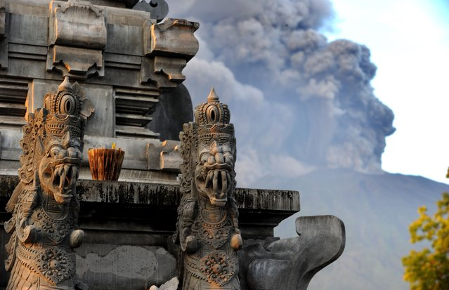 Mount Agung's eruption is seen next to a Balinese temple at Kubu sub-district in Karangasem Regency on Indonesia's resort island of Bali on November 26, 2017. (Photo by Sonny Tumbelaka/AFP Photo)